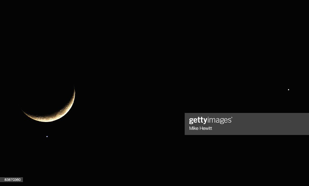 The planet Venus appears close to the crescent Moon as Jupiter (R) appears nearby during a rare planetary alignment on December 1, 2008 in Brighton, England.