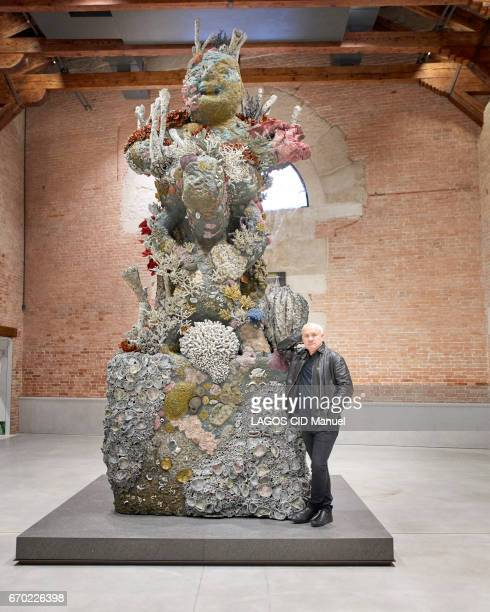 the plastician artist Damien Hirst poses near his artwork Two Figures with a Drum at la Punta Della Dogana on march 20 2017 in Venice Italy