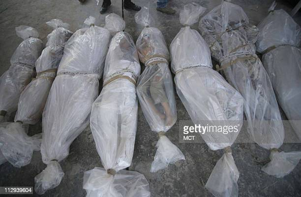 The plasticwrapped bodies of children are lined up outside a hospital in the port city of Tyre Lebanon after an Israeli air strike in the southern...