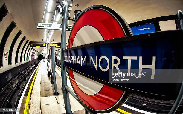 CONTENT] The platform of Clapham North tube station with the London Underground sign on large display