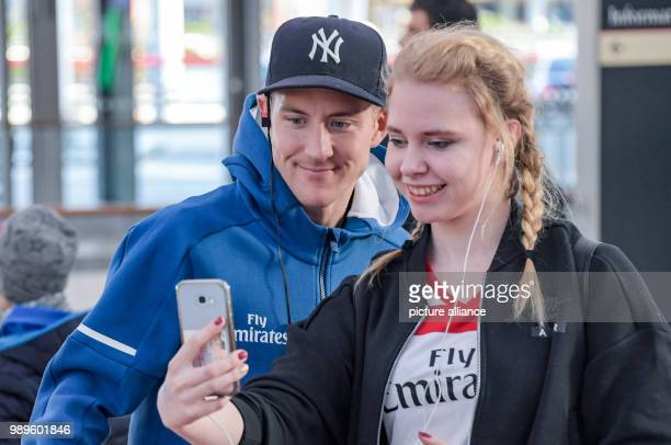 The player of the Hamburger SV soccer club Lewis Holtby takes a photo with a fan in the departure terminal at the airport in Hamburg Germany 1...
