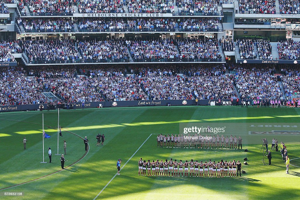 The players and crowd stand for a minutes silence in tribute to Anzac Day during the round five AFL match between the Collingwood Magpies and the Essendon Bombers at Melbourne Cricket Ground on April 25, 2016 in Melbourne, Australia.