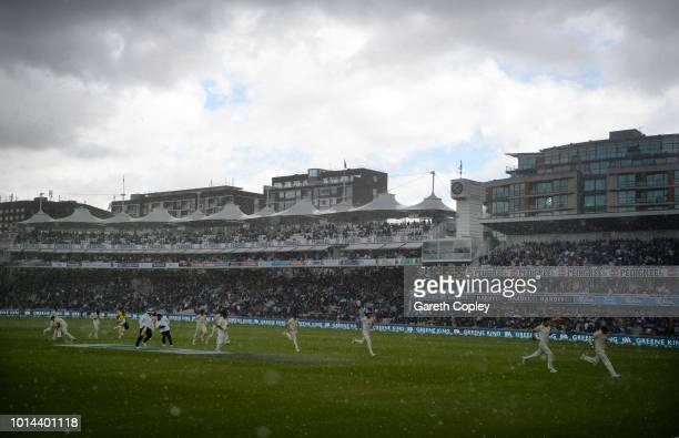 The players and umpires run from the field as heavy rain stops play during day two of the 2nd Specsavers Test between England and India at Lord's...