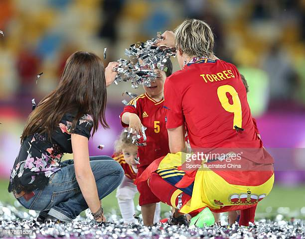 The players' children play in the confetti with Fernando Torres and his wife Olalla Dominguez following victory in the UEFA EURO 2012 final match...
