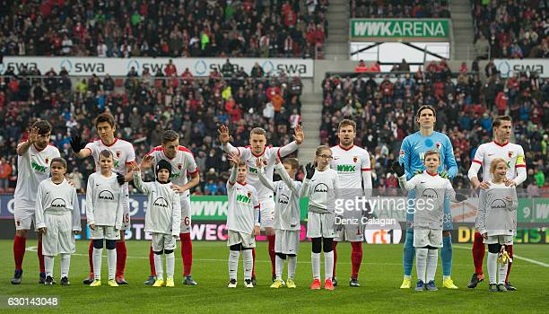 The players enter the pitch with the escort kids prior to the Bundesliga match between FC Augsburg and Borussia Moenchengladbach at WWK Arena on...