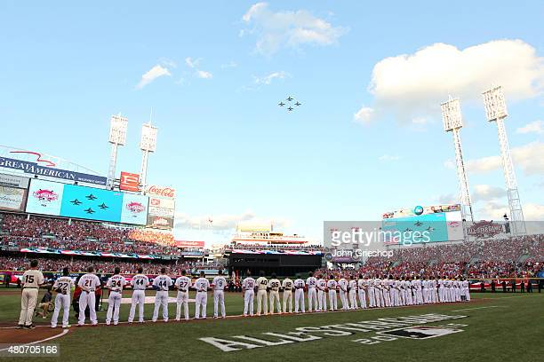 The players for the National League stand along the first base line during the singing of the National Anthem prior to the start of the 86th MLB...