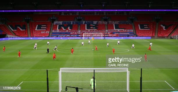 The players kneel before the international friendly football match between England and Wales at Wembley stadium in north London on October 8, 2020. /...