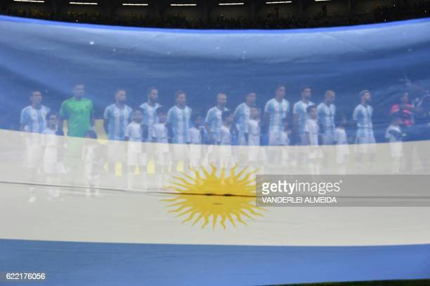 The players of Argentina are seen through an Argentine national flag as they pose for pictures before the start of their 2018 FIFA World Cup...