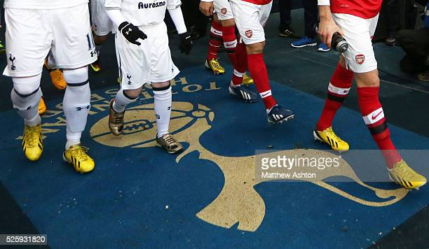 The players of Arsenal and Tottenham Hotspur walk over the Tottenham club badge on the floor