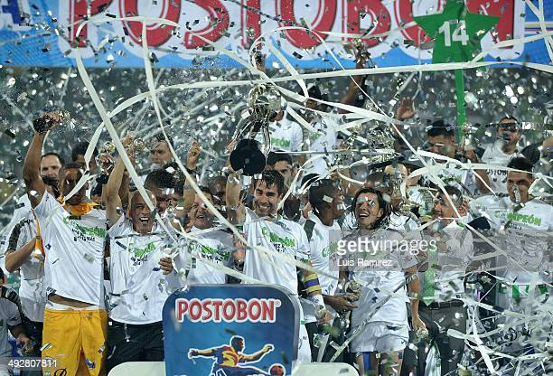 The players of Atletico Nacional lift the cup as champions of the Liga Postobon I 2014 after defeat Atletico Junior during a second leg match between...