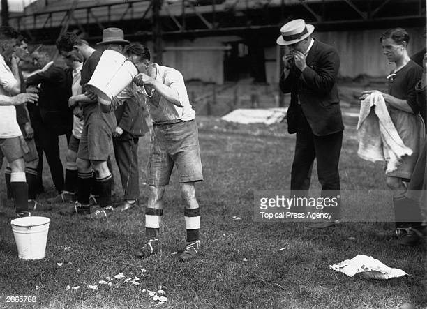 The players of Clapton Orient take their traditional half time refreshments of oranges and water by the side of the pitch.