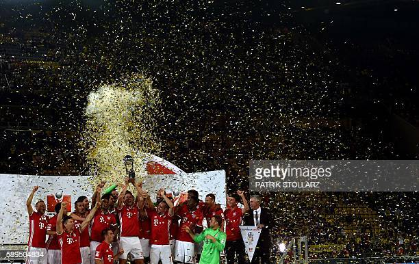 TOPSHOT The players of FC Bayern Munich celebrate with the trophy after their 20 win during the German Super Cup football match final Borussia...