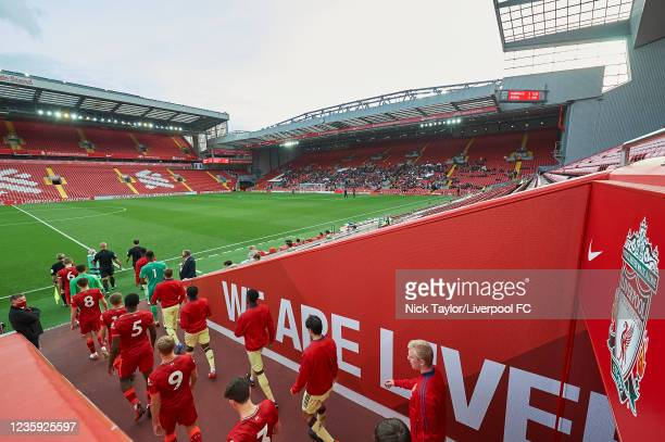 The players of Liverpool and Arsenal make their way to the pitch at the start of the PL2 game at Anfield on October 16, 2021 in Liverpool, England.