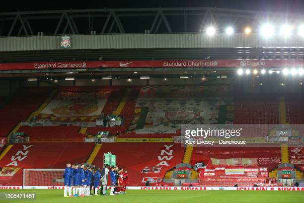 The players of Liverpool and Chelsea line up in front of The Kop stand prior to the Premier League match between Liverpool and Chelsea at Anfield on...