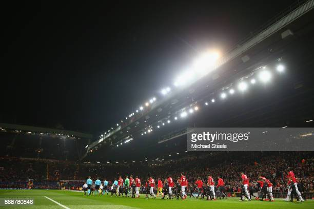 The players of Manchester United and Benfica walk onto the pitch ahead of the UEFA Champions League group A match between Manchester United and SL...
