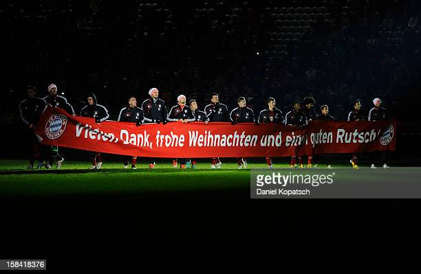 The players of Muenchen show a banner to wish merry christmas and a happy new year to their supporters after the Bundesliga match between FC Bayern...