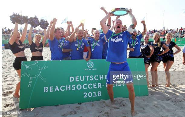 The players of Rostock pose with the trophy after winning the German Beachsoccer League final match between Rostocker Robben and Ibbenbuerener BSC on...