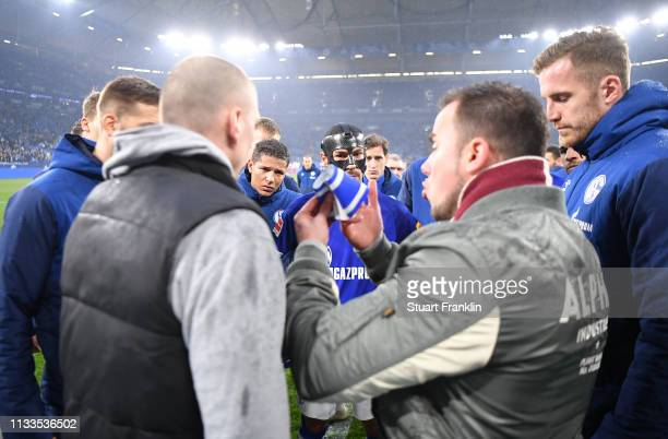 The players of Schalke look on as a fan holds the captains armband during a discussion after the Bundesliga match between FC Schalke 04 and Fortuna...
