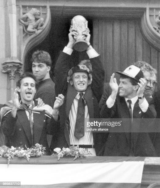 The players of the German national soccer team forward Pierre Littbarski defender Andreas Brehme Lothar Matthaeus cheer laugh and smile as they...
