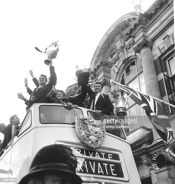 The players of Tottenham Hotspur Football Club wave the Division one championship and FA Cup trophies from an open top bus during a civic reception...