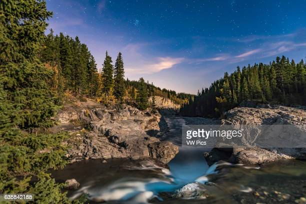The Pleaides star cluster and the stars of late autumn and winter rising over Elbow Falls in Kananaskis Country in Alberta on a moonlit night with a...