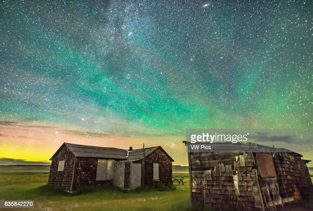 The Pleiades rising behind the rustic cabins and outbuildings of the historic Larson Ranch in Grasslands National Park Saskatchewan Aurora shines to...