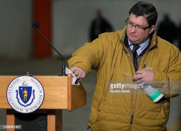 The podium where Massachusetts Governor Charles Baker was to give a speech is sanitized after a New England Patriots jet arrived at Logan Airport in...