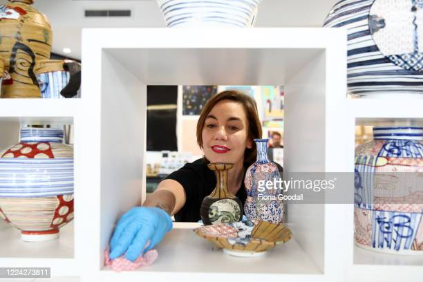 The Poi Room owner MelanieJane Smith cleans surfaces as they prepare for the Ponsonby store to open at level two on May 12 2020 in Auckland New...