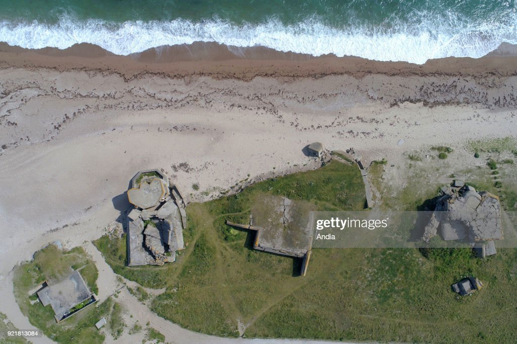 The 'Pointe de Neville' Headland with the former German World War II artillery battery 'Blankenese' in Neville-sur-Mer, part of Germany's Atlantic Wall coastal fortifications. Remains of a bunker on the beach after years of erosion. Coast, beach and blockhouse.