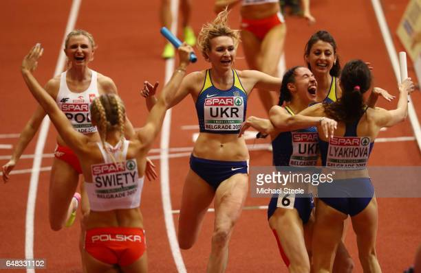 The Poland team and the Ukraine team celebrate winning the gold and bronze medals respectively during the Women's 4x400 metres relay final on day...