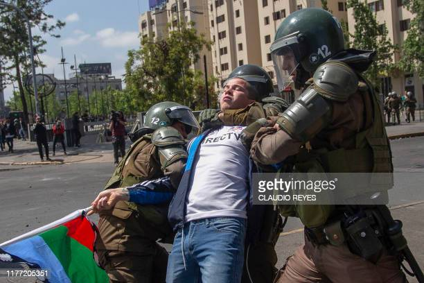TOPSHOT The police arrest a demonstrator during clashes between protesters and the police in Santiago on October 20 2019 Fresh clashes broke out in...