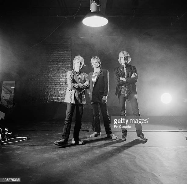 The Police British rock band pose for a group studio portrait against a smoky background with part of a bare brick wall visible United Kingdom circa...