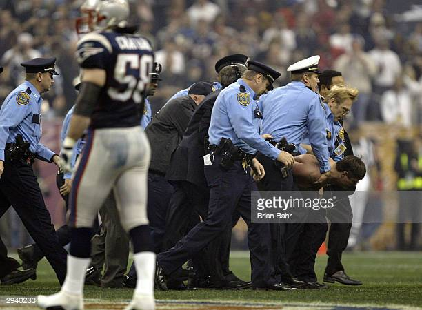 The police carry a streaker off the field during Super Bowl XXXVIII between the New England Patriots and the Carolina Panthers at Reliant Stadium on...