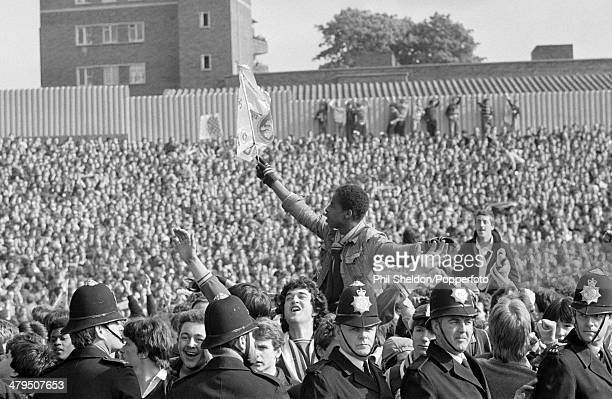 The Police form a barrier on the pitch at Highbury as Aston Villa fans celebrate after winning the First Division Championship following their match...