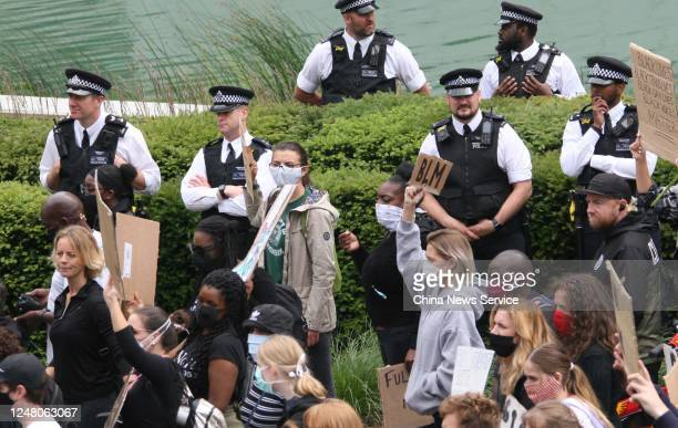 The police guard as protesters participate in a Black Lives Matter demonstration outside the United States Embassy in memory of the death of George...