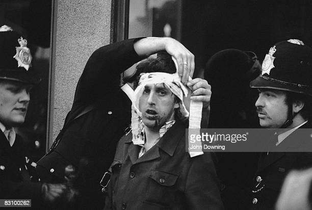 The police help an injured man during the Brixton Riot of 11th April 1981