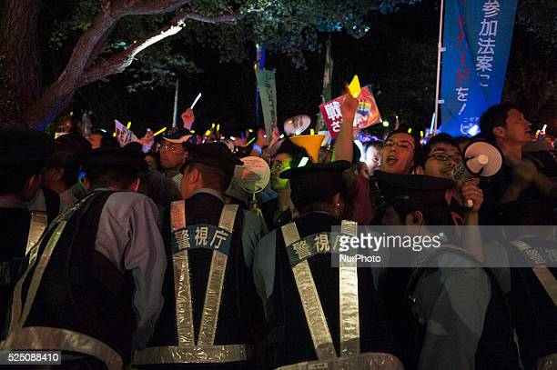 The police push protestors back behind barricades around Diet building during protest against government's security bill in Tokyo Japan on 14...