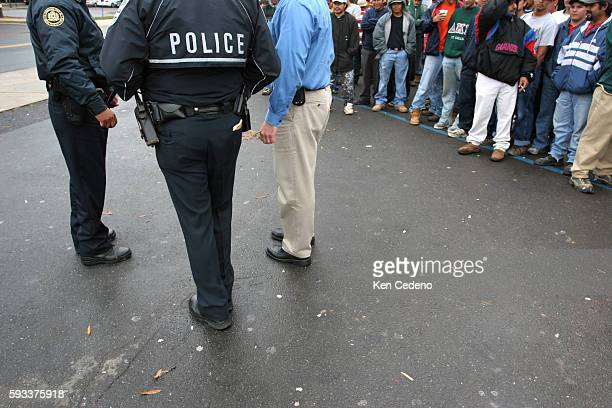 The police speak to a worker as Latino day laborers congregate near a 7Eleven store in Herndon Virginia about 30 miles west of Washington October 13...