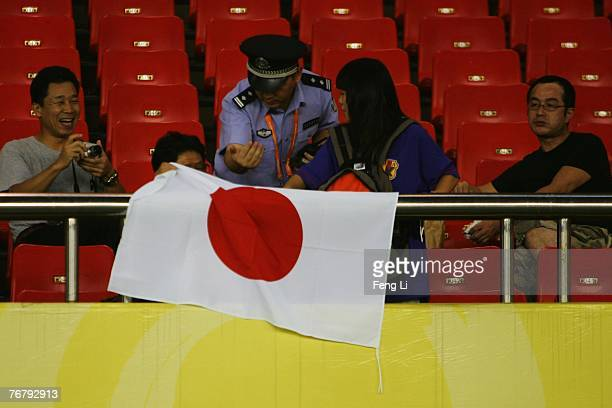The policeman don't let the Japanese fans put the nation flag before the FIFA Women's World Cup 2007 Group A match between Germany and Japan at...