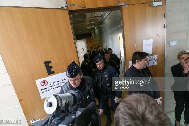 The policemen are watching the entrance of the courtroom in Nanterre on March 15 where the two older children of iconic French musician Johnny...