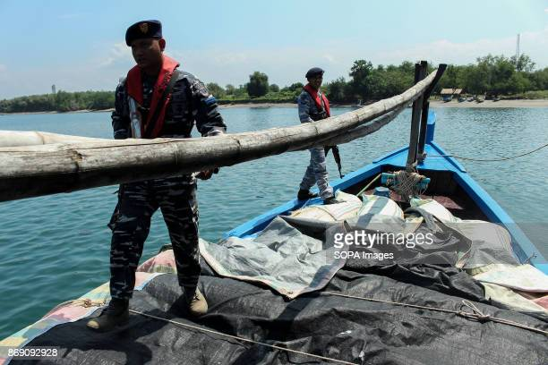 The policemen seen guarding the smuggler's bat with weapon The Indonesian Navy foiled smuggling horseshoe Crab at the port of Krueng GeukuhAmount...