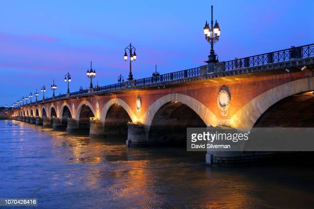 The Pont de Pierre or Stone Bridge which connects the Left and Right banks of the Garonne River is seen at sunset on June 24 2018 in Bordeaux France...