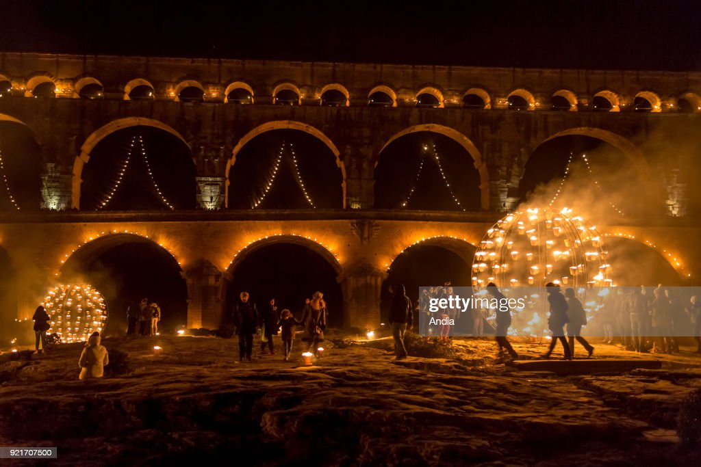 The 'Pont du Gard' bridge, ancient Roman aqueduct that crosses the Gardon River, lit up at night on the occasion of the show entitled 'Nuit des lucioles', an event organised for the 30th anniversary of its registration as a UNESCO World Heritage Site. Night-time show 'Nuit des lucioles' (Firefly's Night), directed by Compagnie Carabosse.