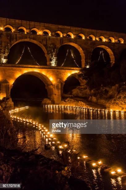 The 'Pont du Gard' bridge ancient Roman aqueduct that crosses the Gardon River lit up at night on the occasion of the show entitled 'Nuit des...