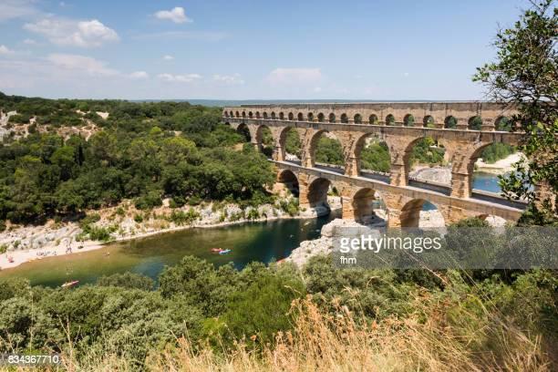 the pont du gard - famous ancient roman aqueduct crosses gardon river (gard/ france) - pont du gard stockfoto's en -beelden