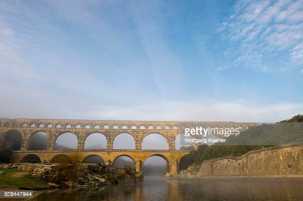 The Pont du Gard on a foggy morning was built in the first century AD is an ancient Roman aqueduct that crosses the Gardon River in the south of...