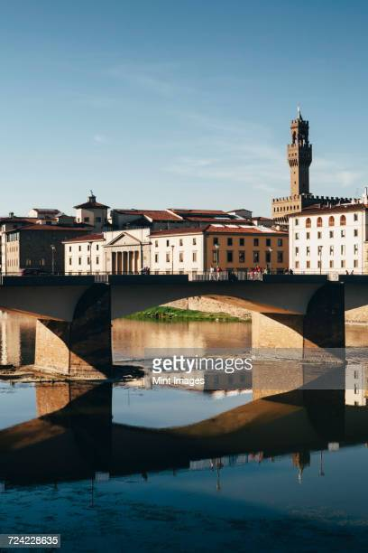 The Ponte alle Grazie, historic bridge over the flat calm water of the River Arno, in the middle of Florence.