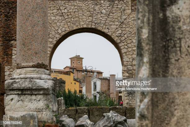 the pontifical university of saint thomas aquinas as seen from an arch in the roman forum - rome, italy - saint thomas aquinas stock pictures, royalty-free photos & images