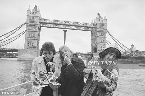 The pop group 'Wings' left to right Paul McCartney wife Linda and Denny Lane eat fish and chips from newspaper on boat trip down the River Thames...