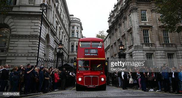 The poppy appeal bus leaves 10 Downing Street on October 30 2014 in London England The classic 1960s Routemaster bus toured London to support the...